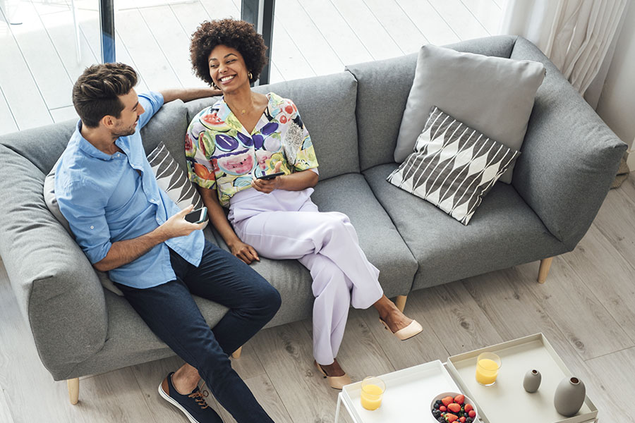Contact - Smiling Couple Sitting On Couch Using Smartphones