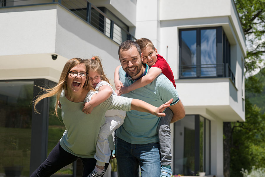 Personal Insurance - Portrait Of Excited Family Standing Outside Modern Home